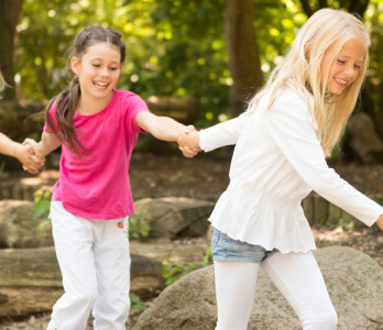 Kinder die sich an den Händen halten und auf dem Spielplatz sind
